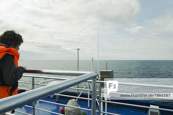Junge  der den Horizont beobachtet  auf dem Oberdeck eines Bootes.