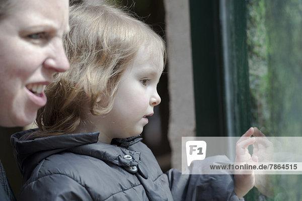 Mutter und Tochter schauen gemeinsam durchs Fenster
