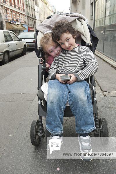 Junge Geschwister sitzen zusammen im Kinderwagen
