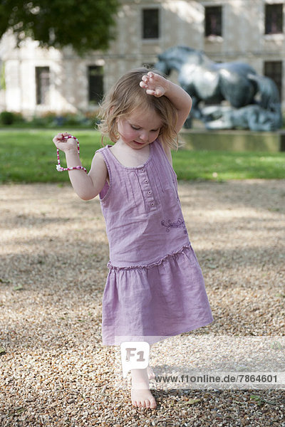 Little girl walking on gravel