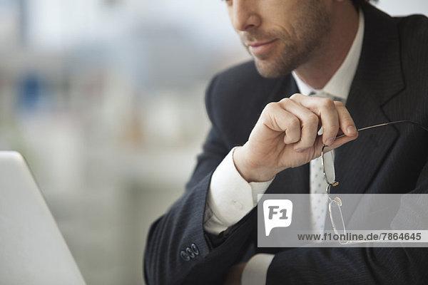 Geschäftsmann sitzend mit Brille in der Hand  beschnitten
