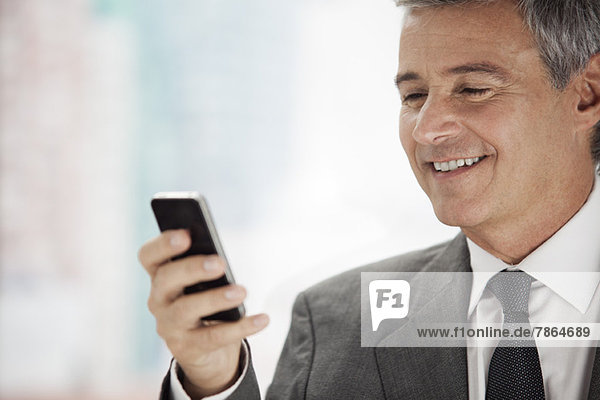 Business executive looking at cell phone  smiling