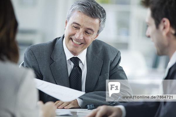 Geschäftsmann lächelt im Gespräch mit Kollegen