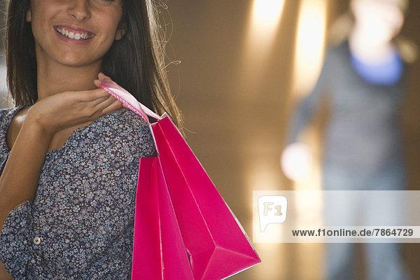 Junge Frau mit Einkaufstaschen  beschnitten