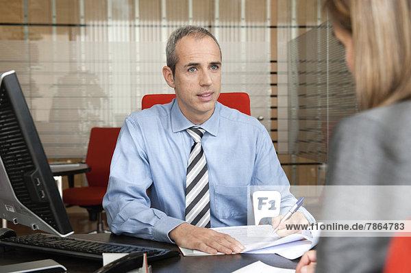 Geschäftsmann  der den Kunden im Büro unterstützt.