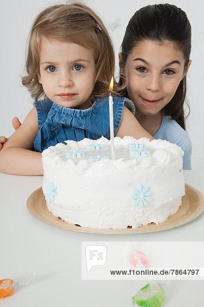 Junge Schwestern mit Geburtstagskuchen