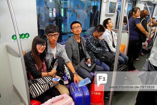 China  Shanghai  Luwan District  Xintiandi Metro Station  subway  public transportation  Lavender Line 10  Mandarin symbols  hanzi  Asian  man  woman  couple  riders  sitting .