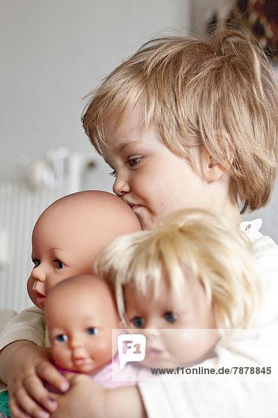 Blondes Mädchen umarmt ihre Puppen