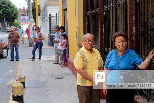 Lima  Hauptstadt  stehend  Städtisches Motiv  Städtische Motive  Straßenszene  Straßenszene  Senior  Senioren  Frau  Mann  Soziale Beziehung  warten  Weg  Hispanier  reifer Erwachsene  reife Erwachsene  Nachbarschaft  Bushaltestelle  Haltestelle  Peru