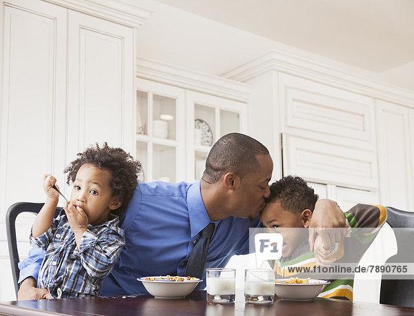 Menschlicher Vater  Sohn  küssen  Tisch  Frühstück