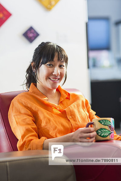 Asian woman having cup of coffee in armchair