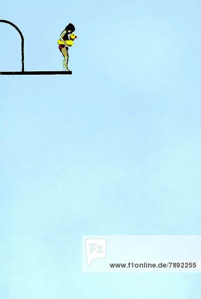 Mädchen mit Schwimmreifen steht am Rand eines Sprungturms