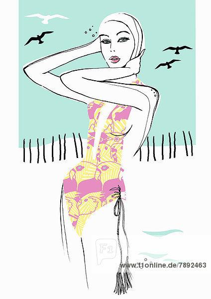 Elegante Frau mit Badeanzug und Badekappe am Strand