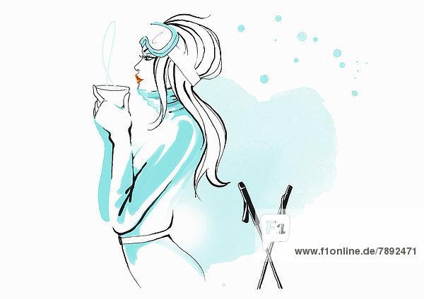 Skifahrerin trinkt ein heißes Getränk