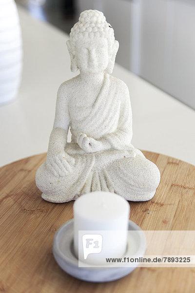 Nahaufnahme einer Buddha-Statue mit einer Kerze auf einem Tisch