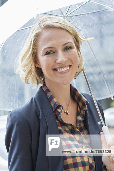 Portrait of a smiling woman with an umbrella