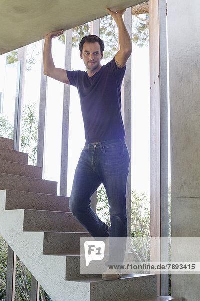 Mann steht zu Hause auf einer Treppe