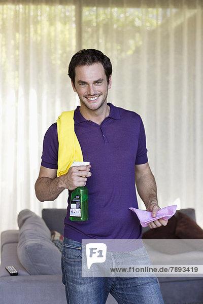 Mann hält Reinigungsgeräte und lächelt