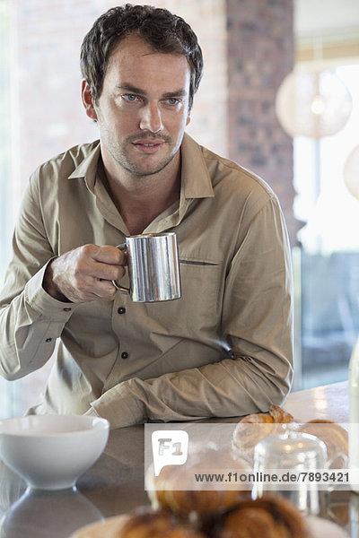 Mann trinkt Tee in der Küche