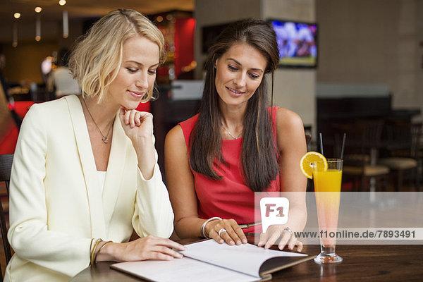 Zwei Freundinnen beim Betrachten der Speisekarte in einem Restaurant