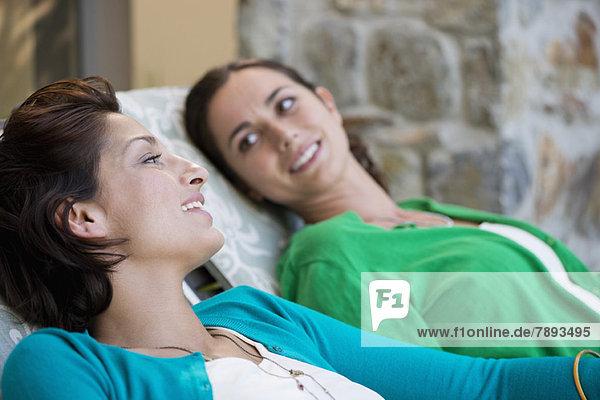 Zwei Frauen entspannen sich auf Liegestühlen