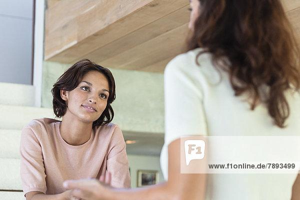 Zwei Freundinnen diskutieren zu Hause.