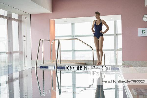 Frau am Pool stehend mit den Händen auf den Hüften