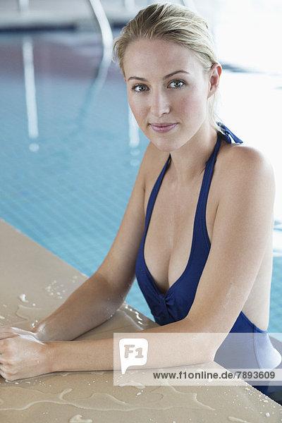 Frau  die sich am Rande eines Swimmingpools lehnt