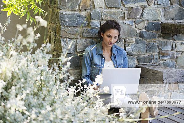 Frau  die sich an eine Steinmauer lehnt und einen Laptop benutzt.