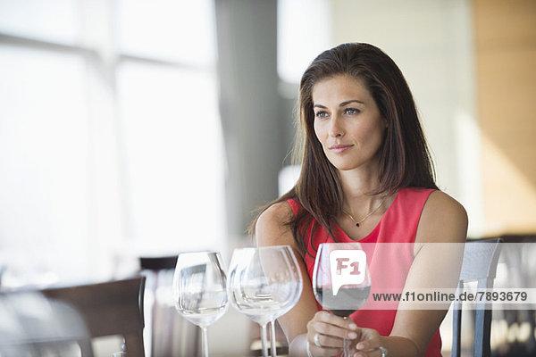 Frau hält ein Weinglas und denkt in einem Restaurant. Frau hält ein Weinglas und denkt in einem Restaurant.