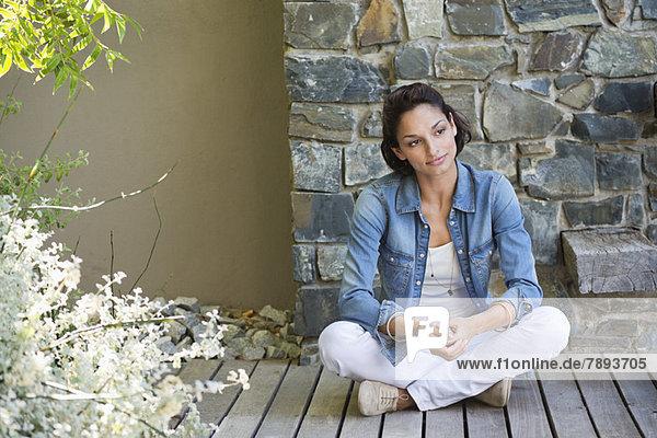 Frau auf einem Hartholzboden sitzend und träumend
