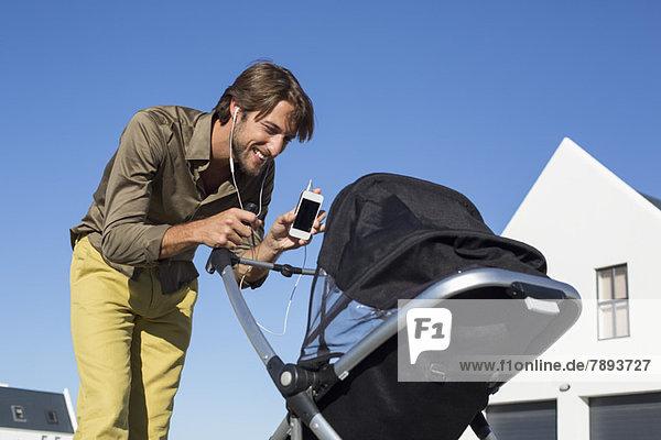 Mann zeigt Handy einem Baby im Kinderwagen