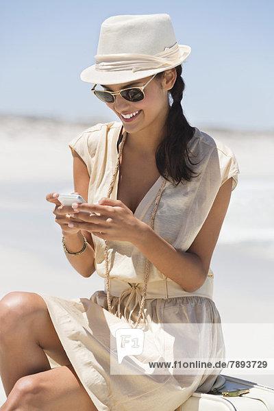 Schöne Frau SMS auf einem Handy am Strand