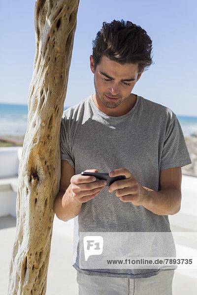 Mann liest Textnachricht auf einem Mobiltelefon