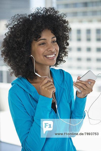 Lächelnde Frau beim Musikhören auf dem Handy
