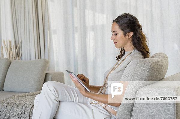 Schöne Frau mit einem digitalen Tablett und Lächeln auf der Couch