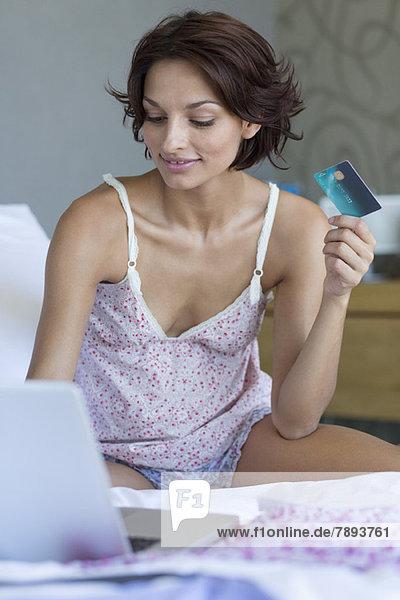 Frau mit Kreditkarte und Arbeit am Laptop