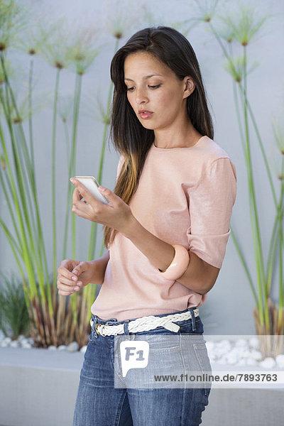 Frau beim Lesen einer SMS auf dem Handy
