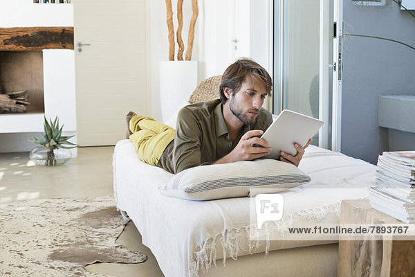 Man using a digital tablet on the bed