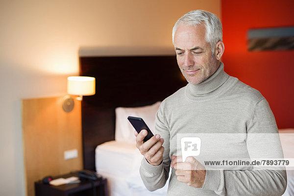 Ein Mann  der ein Handy in einem Hotelzimmer benutzt.