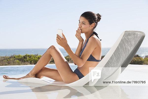 Schöne Frau Videoanrufe auf dem Handy beim Sonnenbaden am Strand