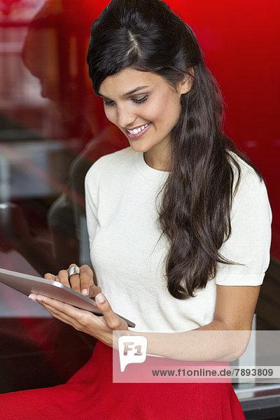 Frau  die ein digitales Tablett benutzt und lächelt