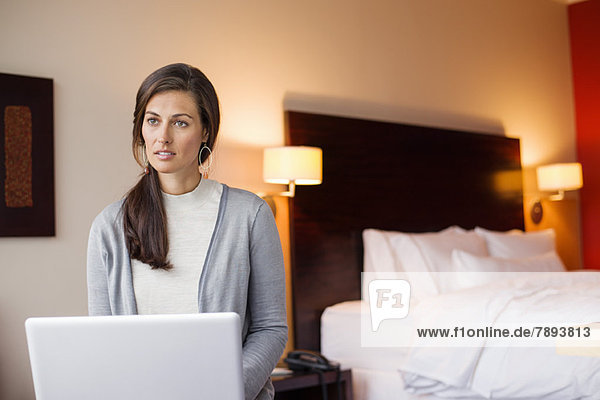 Frau mit Laptop im Hotelzimmer
