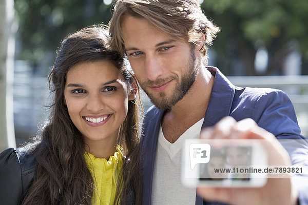 Paar fotografiert sich selbst mit dem Handy