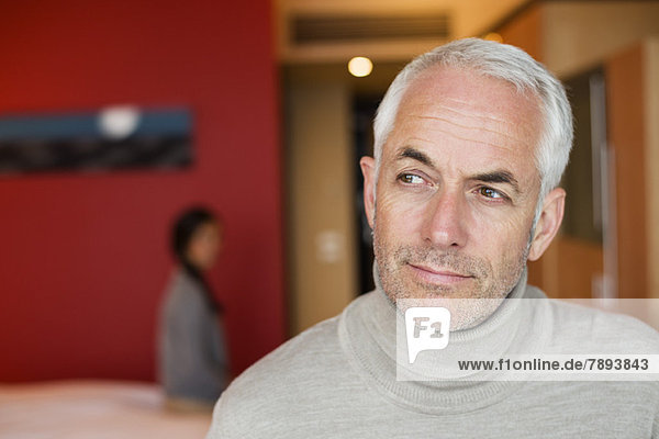 Mann denkt in einem Hotelzimmer mit seiner Frau im Hintergrund