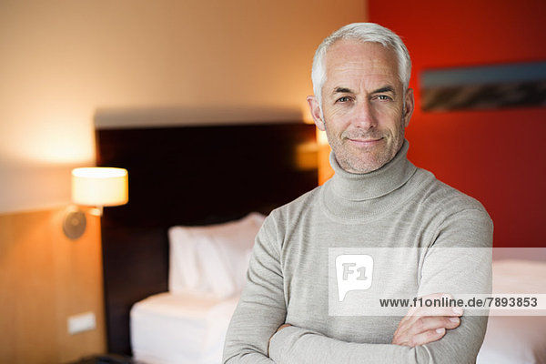 Portrait of a man smiling with arms crossed in a hotel room