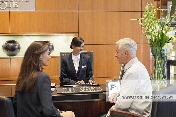 Geschäftsleute im Gespräch an der Hotelrezeption