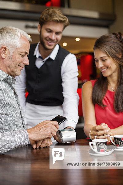 Kellner zeigt einem Paar auf einem Tisch in einem Restaurant ein Kreditkartenlesegerät.