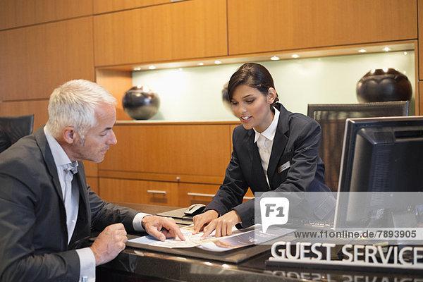 Rezeptionistin  die einem Geschäftsmann eine Broschüre an einem Hotelrezeptionsschalter vorlegt