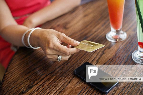 Frau  die mit einer Kreditkarte auf einem Tisch in einem Restaurant bezahlt.